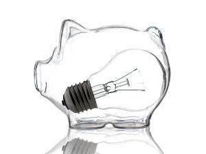 Conceptual shot of incandescent light bulb placed inside glass piggy bank on white background