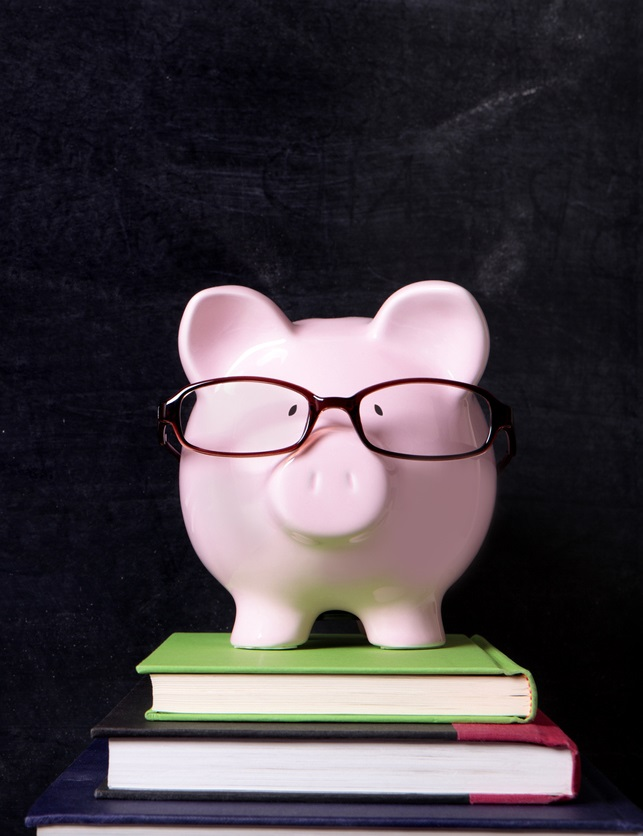 Piggy Bank with Glasses on Stack of Books Behind Blackboard