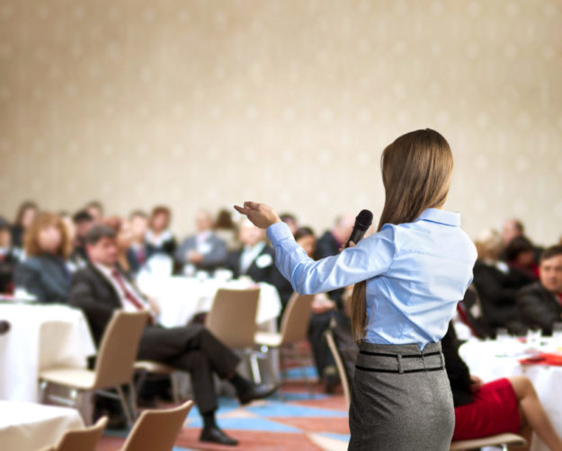 Young woman speaks to tabled audience at business conference
