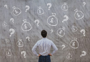 Man in front of wall money bags question marks