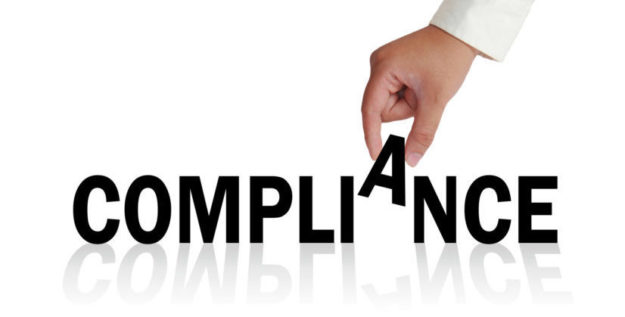 Hand spelling out the word compliance management system