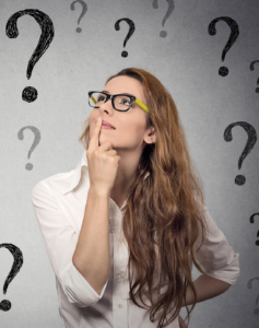 Woman in glasses surrounded by question marks